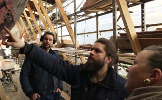 Trebåtbyggerlærling Gudmundur Nordbud forklarer Kulturringens Kristine om de forestående restaureringsarbeidene. Fagansvarlig Caper Hillestad er med på omvisningen.