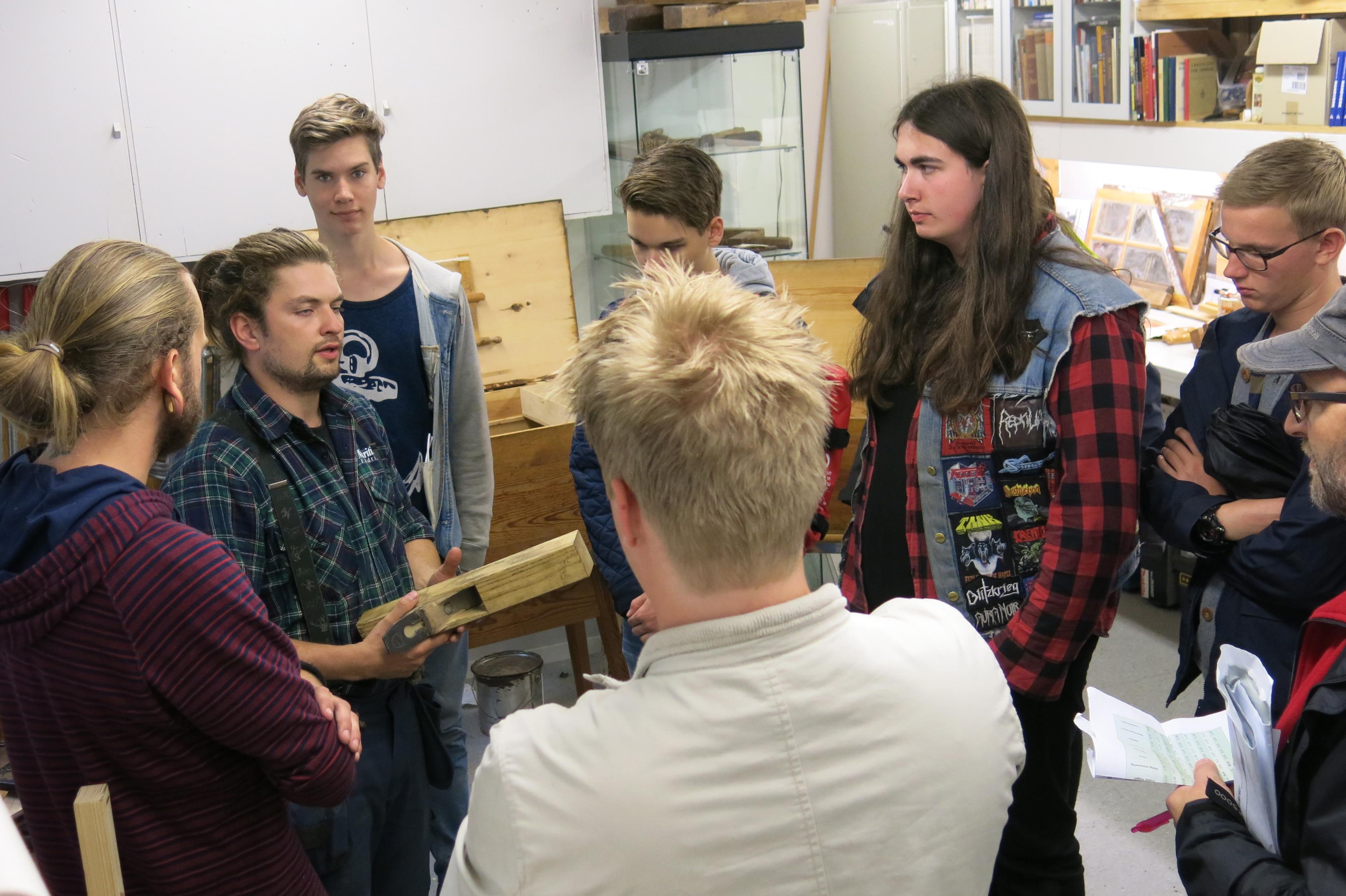 Lyttende elever når trebåtbyggerlærling Gudmundur formidler faget på Håndverksdagene